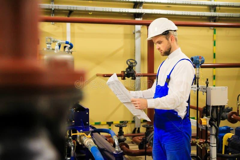 Coordenador com os desenhos na planta de aquecimento Trabalhador industrial do técnico fotografia de stock
