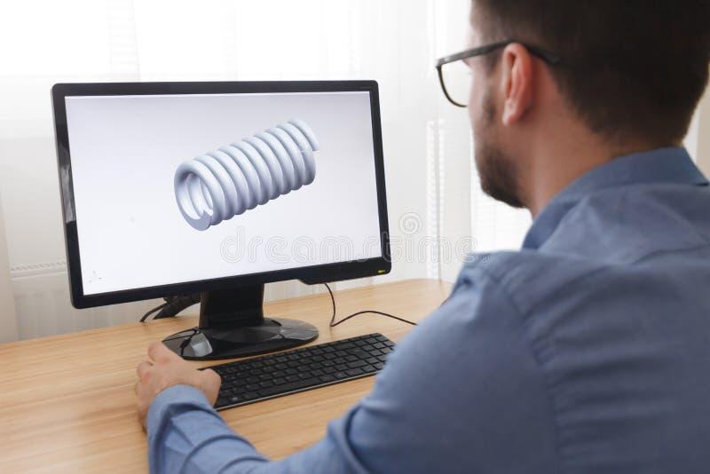 Coordenador, construtor, desenhista no funcionamento de vidros em um computador pessoal É criar, projetando um modelo 3D novo de foto de stock royalty free