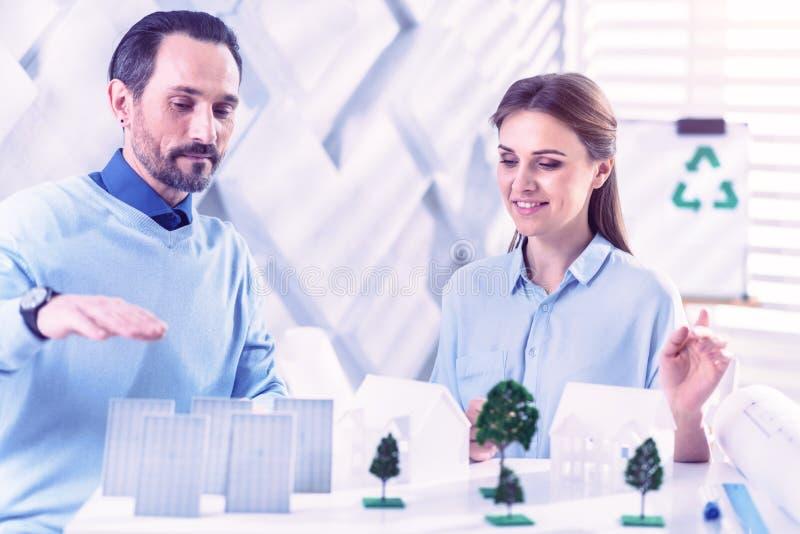 Coordenador da calma que mostra baterias solares ao sentar-se com seu colega imagem de stock