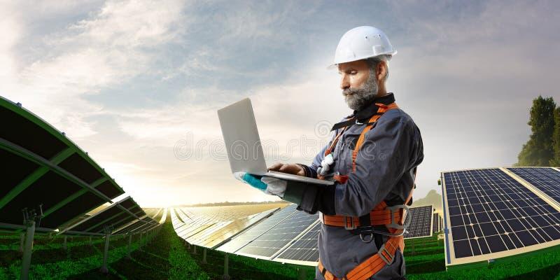Coordenador da energia solar que usa o portátil para a estação da verificação imagem de stock royalty free