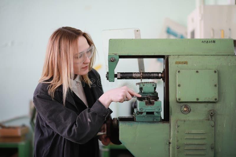 Coordenador da jovem mulher que trabalha na máquina-instrumento fotografia de stock royalty free