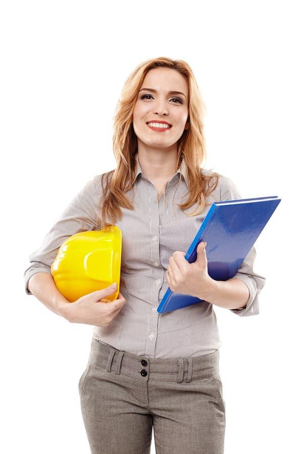 Coordenador da mulher que guarda um plano da construção e um capacete fotografia de stock