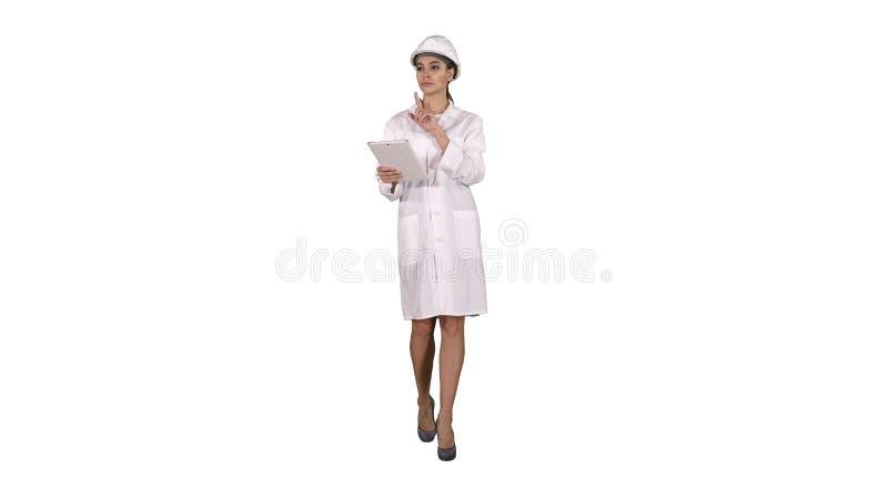 Coordenador da mulher que verifica a informação e os objetos em sua tabuleta no fundo branco foto de stock royalty free