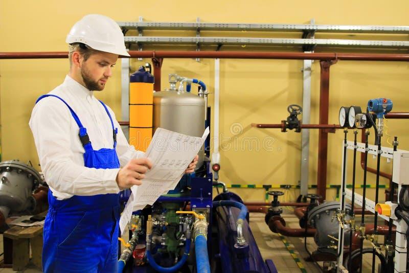 Coordenador de aquecimento com os desenhos na planta industrial foto de stock