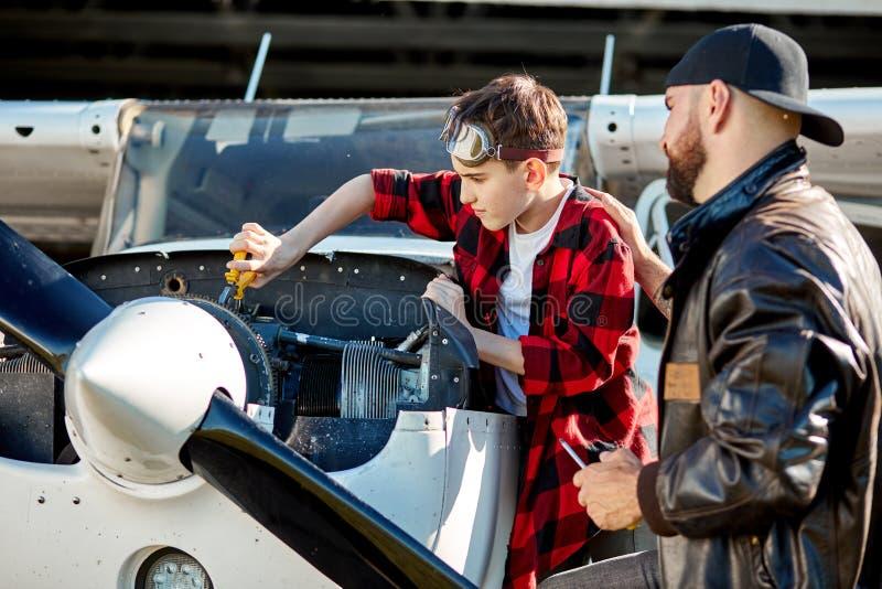 Coordenador de aviação que dá istructions ao rapaz pequeno como fazer a fixação do mecânico do motor do avião fotografia de stock