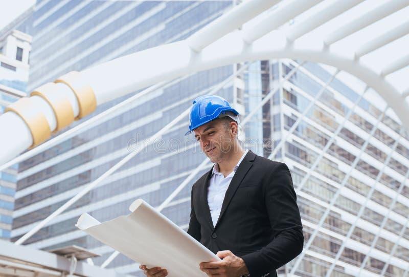 Coordenador de construção masculino guardando os modelos que leem detalhes do funcionamento de projeto foto de stock