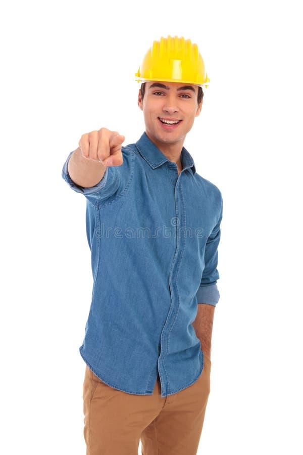 Coordenador de construção novo que veste o capacete amarelo que aponta o finge foto de stock royalty free