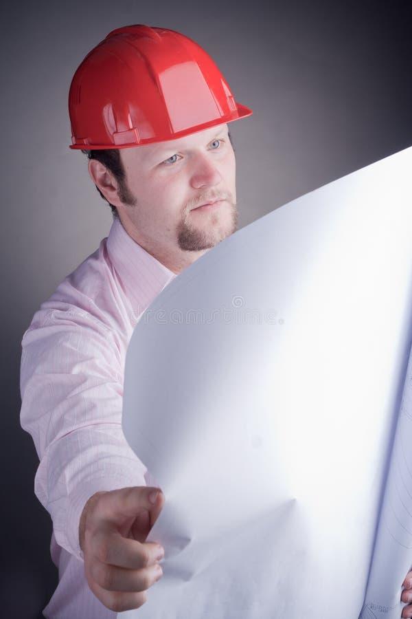 Coordenador de construção que examina o projeto aberto foto de stock royalty free