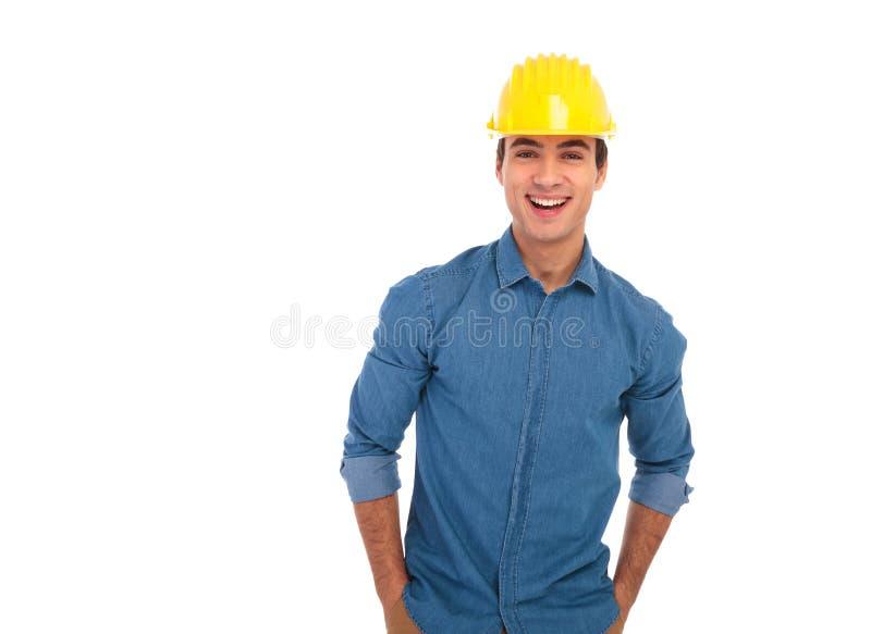 Coordenador de construção relaxado com mãos no riso dos bolsos imagens de stock royalty free