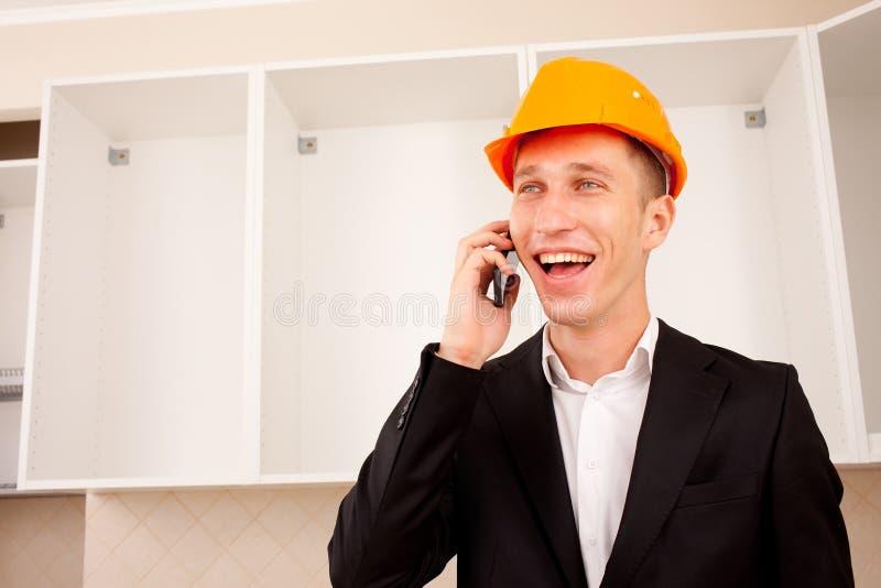 Coordenador de sorriso que fala no telefone no interior fotografia de stock