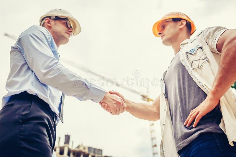 Coordenador do arquiteto que agita as mãos a outra mão no canteiro de obras Trabalhos de equipa do negócio, cooperação, collabora fotografia de stock