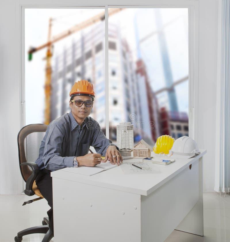 Coordenador do arquiteto que trabalha na sala do escritório contra o const da construção foto de stock