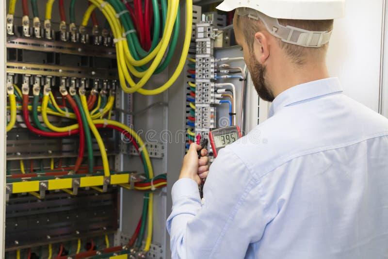 Coordenador do eletricista no trabalho que inspeciona a conexão de expedição de cabogramas da linha elétrica do poder de alta ten fotografia de stock