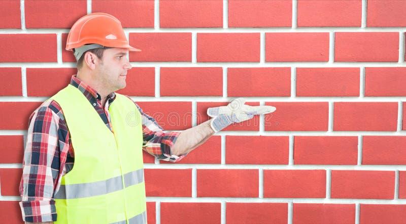Coordenador do homem da construção que mostra sua palma aberta foto de stock
