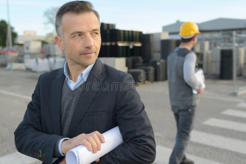 Coordenador e arquiteto que trabalham no canteiro de obras com modelo fotografia de stock