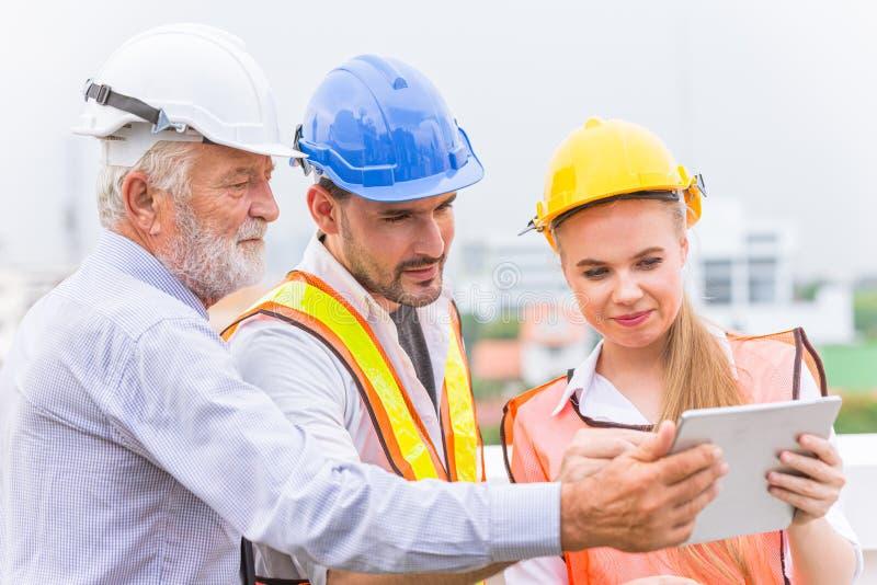 Coordenador e arquitetura do construtor usando a nova tecnologia da tabuleta para ajudar seus trabalhos fotos de stock royalty free