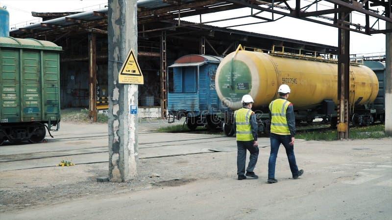 Coordenador e contramestre na fábrica grampo Dois trabalhadores na fábrica em capacetes protetores imagens de stock royalty free