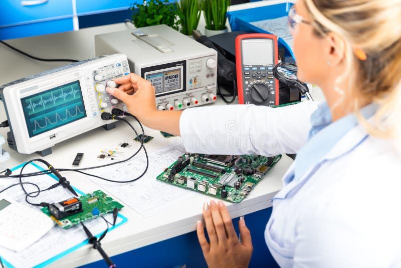 Coordenador eletrônico fêmea que usa o osciloscópio no laboratório fotos de stock