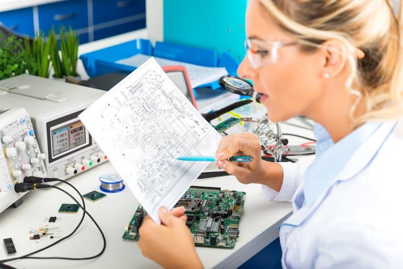 Coordenador eletrônico fêmea que verifica o circuito eletrônico no labora fotografia de stock