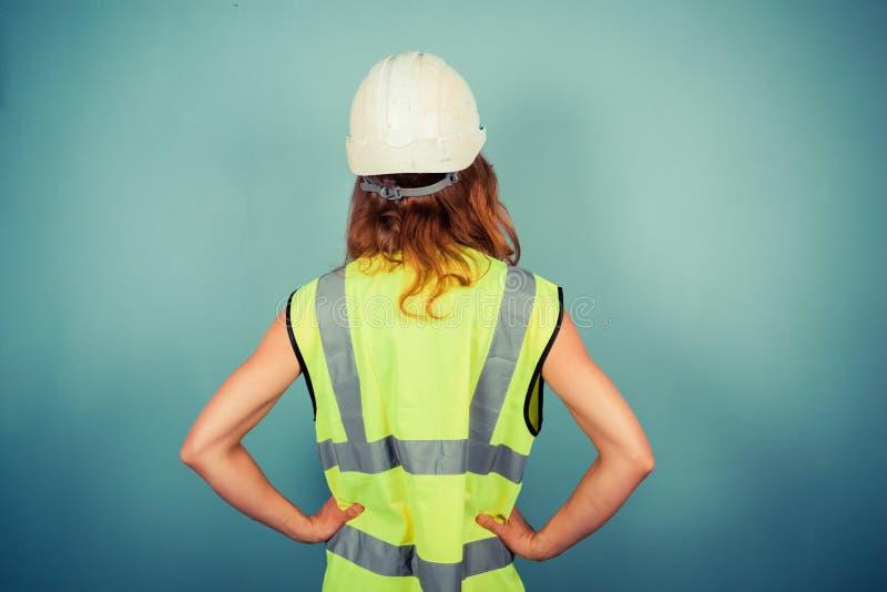 Coordenador fêmea novo no vis e no capacete de segurança altos fotos de stock