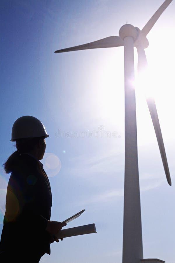 Coordenador fêmea novo que guarda modelos e que verifica turbinas eólicas no local, silhueta fotos de stock royalty free