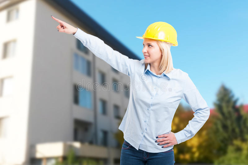 Coordenador fêmea que veste o capacete amarelo que aponta algo fotografia de stock