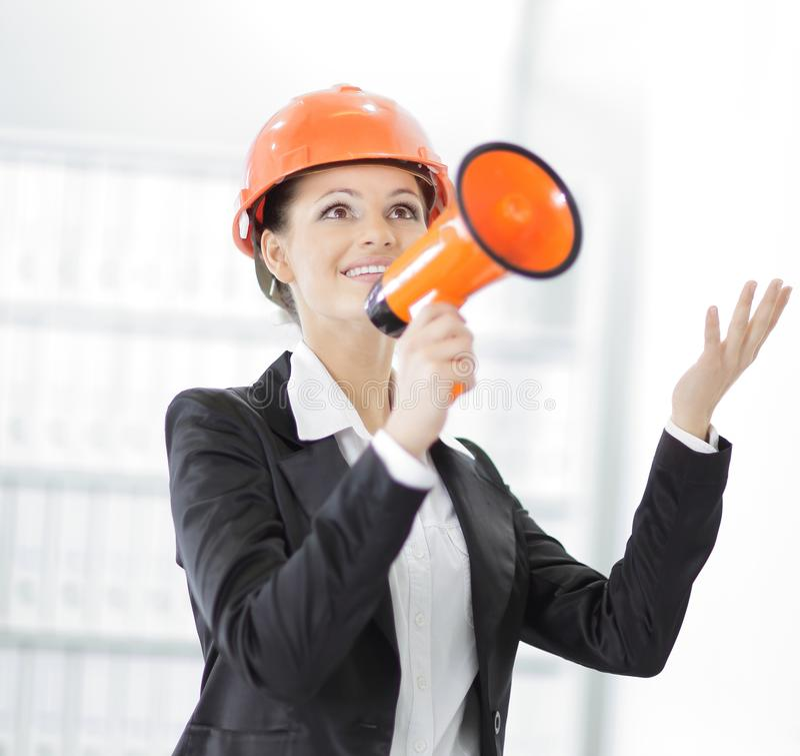 Coordenador fêmea seguro com um megafone no fundo do escritório imagens de stock