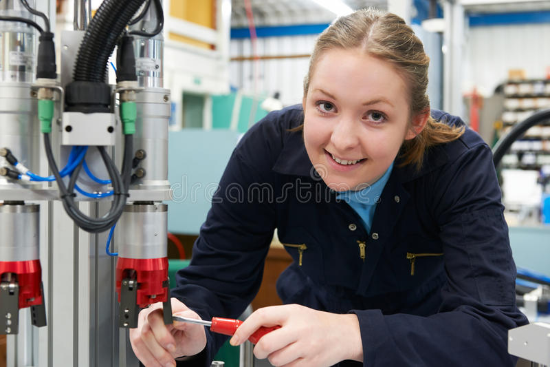 Coordenador fêmea Working On Machinery do aprendiz na fábrica imagem de stock