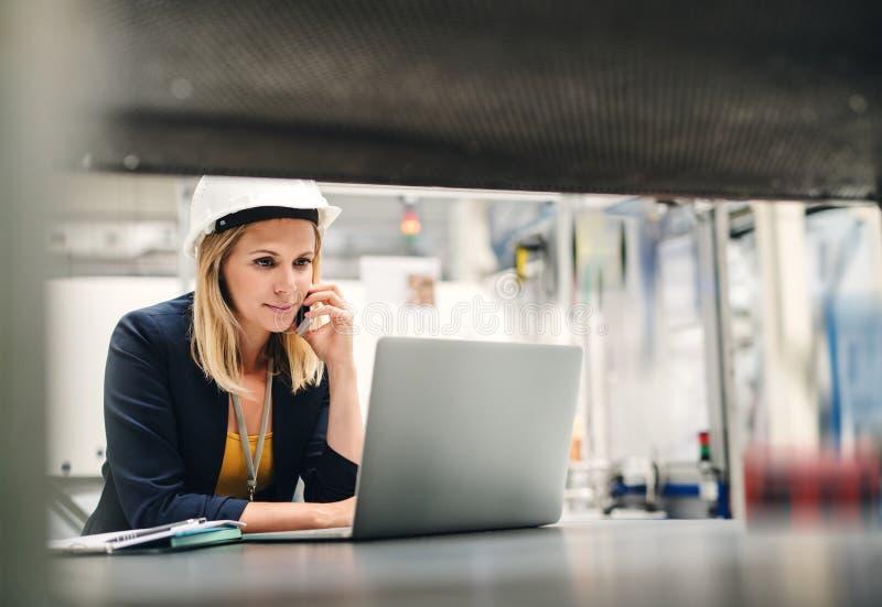 Coordenador industrial da mulher em uma fábrica usando o portátil e o smartphone imagem de stock royalty free