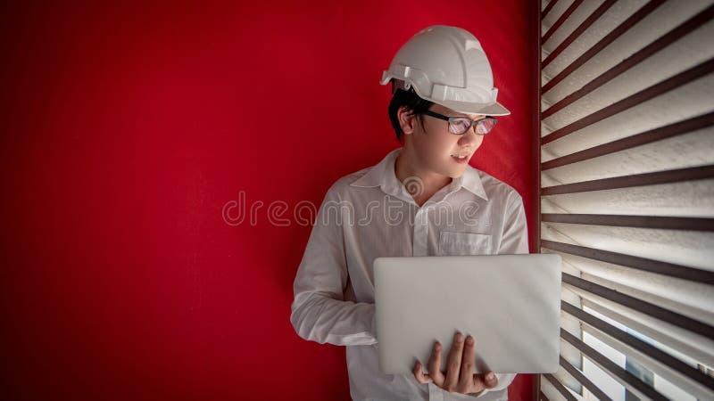 Coordenador masculino asiático com o capacete que trabalha com portátil imagens de stock