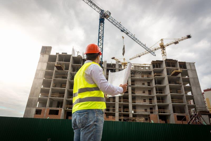 Coordenador masculino na veste e no capacete de segurança da segurança que olham a construção da construção nova imagens de stock