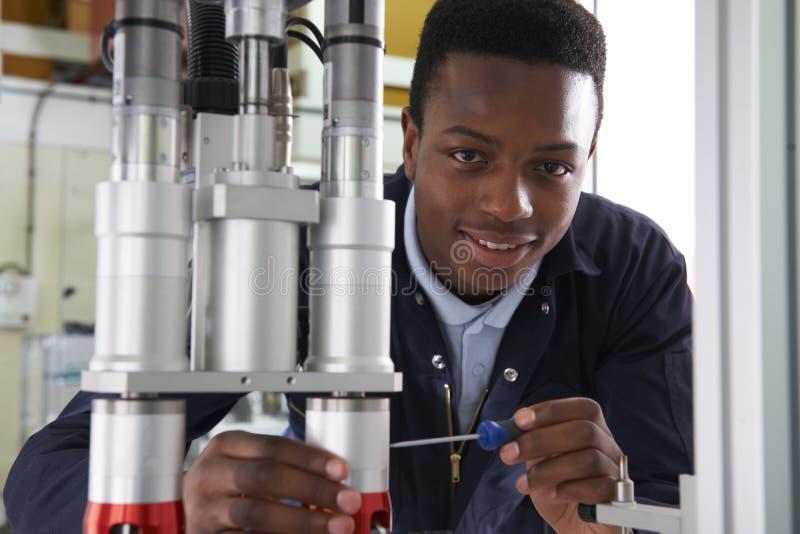 Coordenador masculino Working On Machine do aprendiz na fábrica imagem de stock