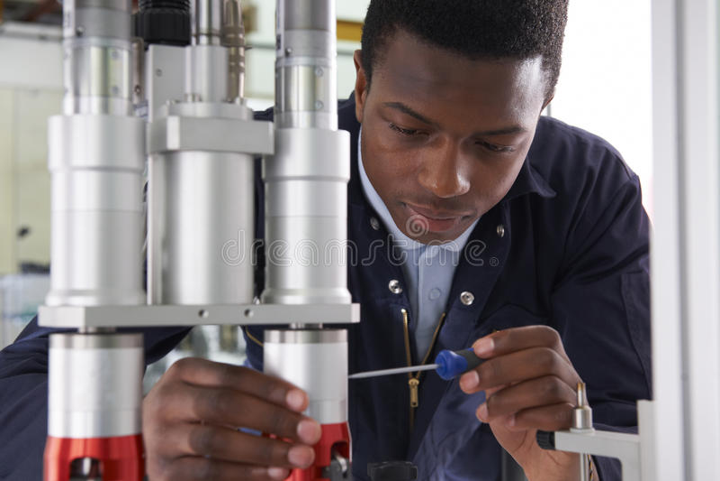 Coordenador masculino Working On Machine do aprendiz na fábrica foto de stock royalty free