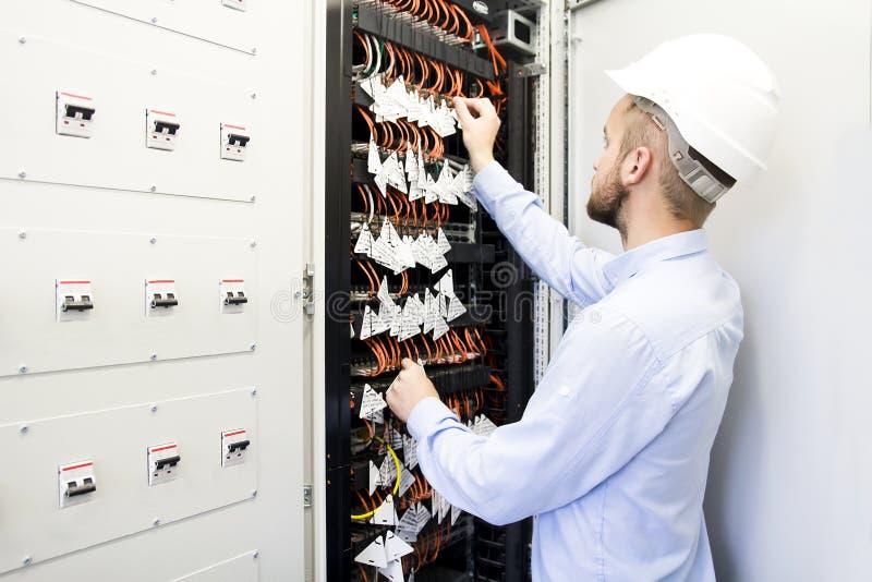 Coordenador no centro de dados Trabalhador em um capacete perto dos interruptores de cabos óticos fotos de stock