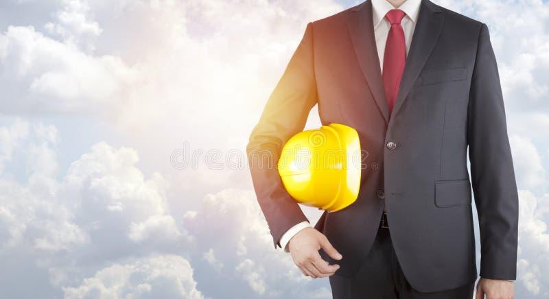 Coordenador no terno preto que guarda o capacete amarelo no céu azul ensolarado fotos de stock royalty free
