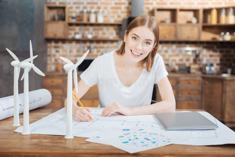 Coordenador novo positivo que sorri ao sentar-se na tabela e na tiragem foto de stock