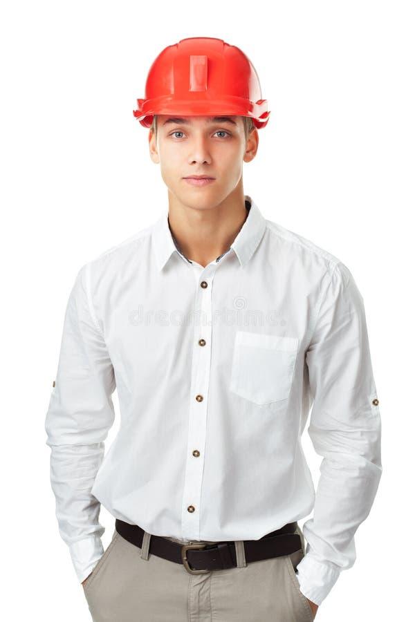 Coordenador novo que veste a posição vermelha do capacete fotos de stock royalty free