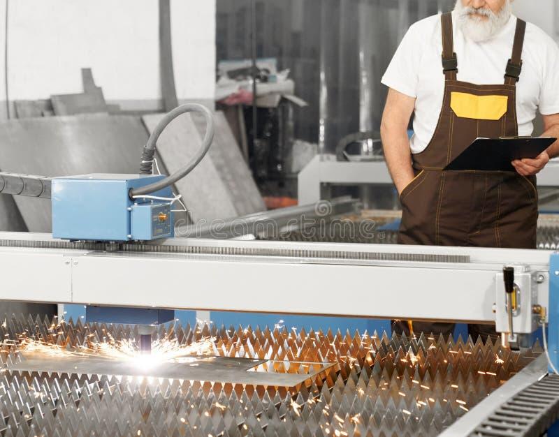 Coordenador observando o laser do plasma cortar a folha de metal imagens de stock