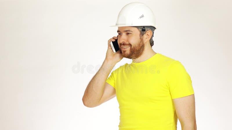 Coordenador ou arquiteto considerável de construção no tshirt amarelo que falam em seu telefone celular contra o fundo branco fotos de stock