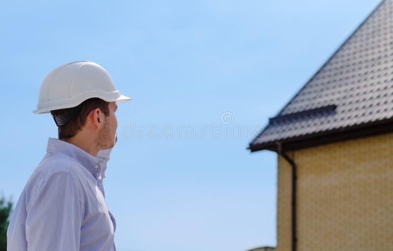 Coordenador ou inspetor de construção que verifica um telhado imagens de stock
