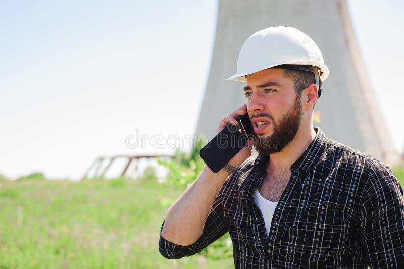 Coordenador profissional do eletricista em um capacete branco no local de trabalho imagem de stock