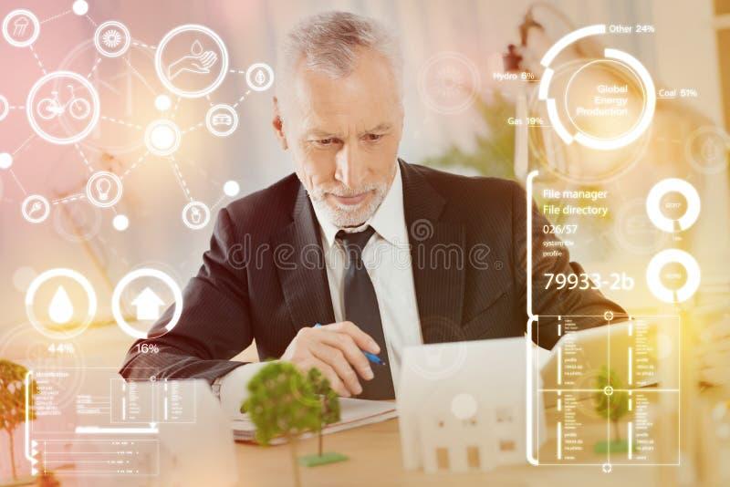 Coordenador qualificado que olha a casa e o pensamento diminutos fotografia de stock royalty free