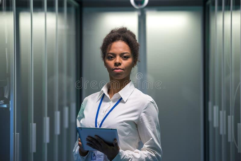 Coordenador sério no corredor do centro de dados fotografia de stock