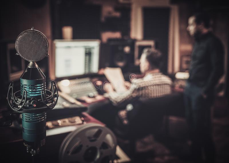 Coordenador sadio e produtor que trabalham junto no painel de mistura no estúdio de gravação do boutique foto de stock