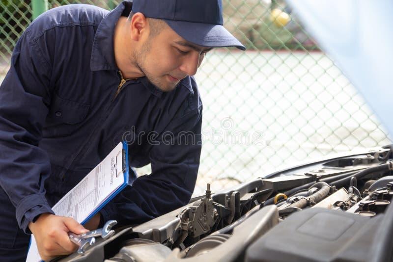 Coordenadores e técnicos do auto mecânico do especialista na estação do serviço do carro, verificando máquinas do motor de automó imagens de stock