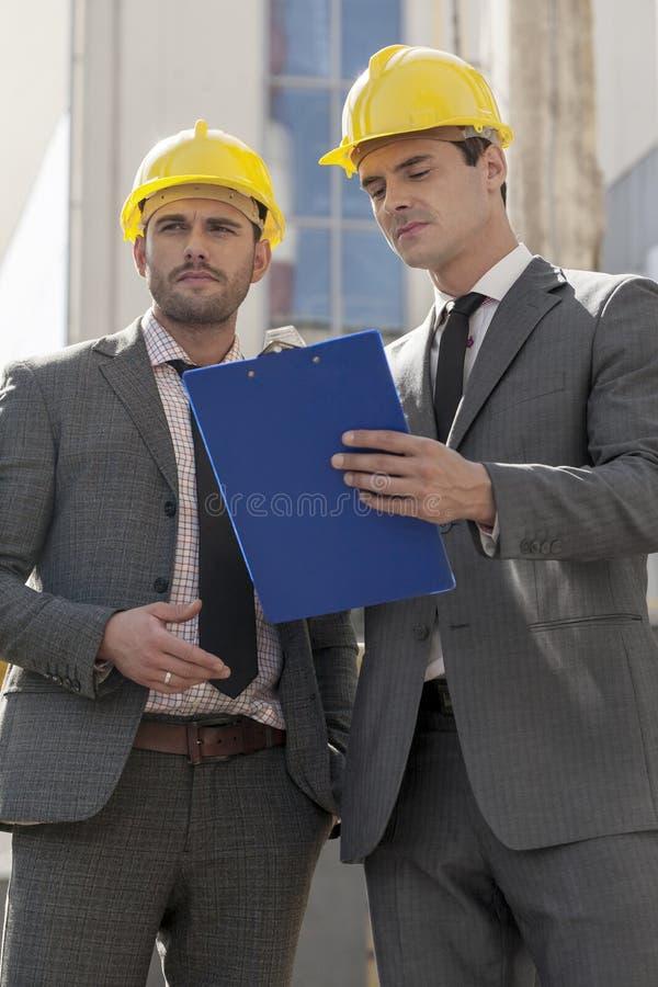 Coordenadores masculinos novos com prancheta que discutem no canteiro de obras imagem de stock