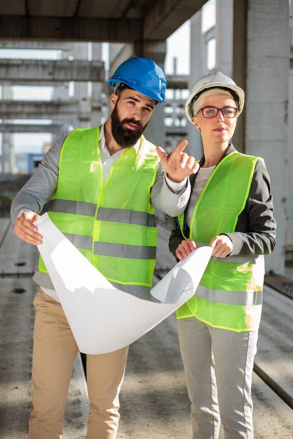 Coordenadores novos ou sócios comerciais fêmeas e masculinos no canteiro de obras, discutindo planos e examinando trabalhos Arq imagem de stock