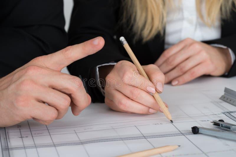 Coordenadores que discutem sobre o modelo na mesa fotografia de stock