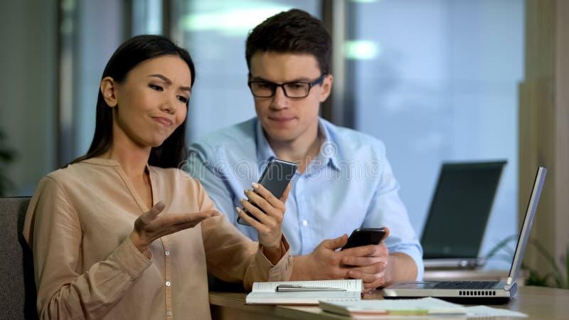 Coordenadores que testam o smartphone novo, decepcionado com qualidade de software, grupo de teste foto de stock