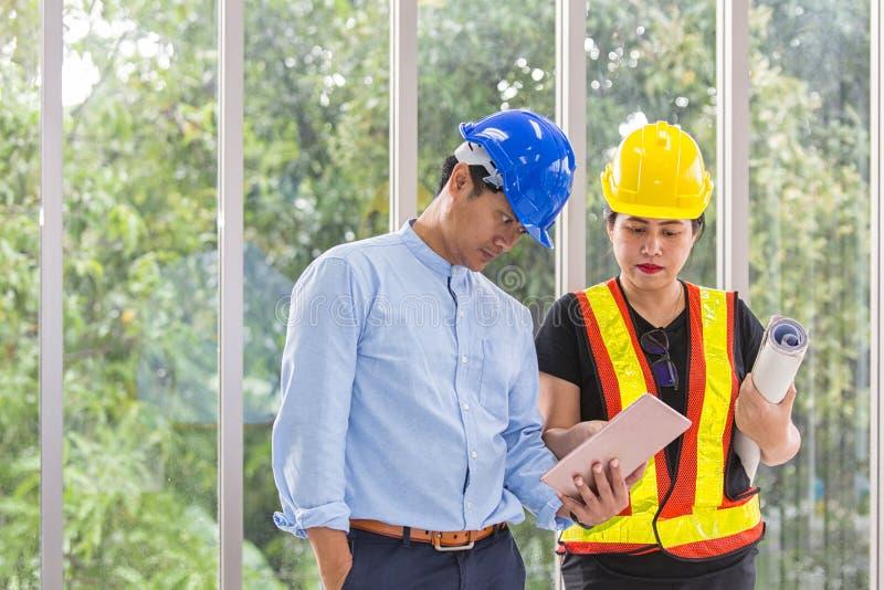 Coordenadores que trabalham a sala de reunião com uma tabuleta Dois trabalhadores estão olhando o plano da construção no escritór fotos de stock